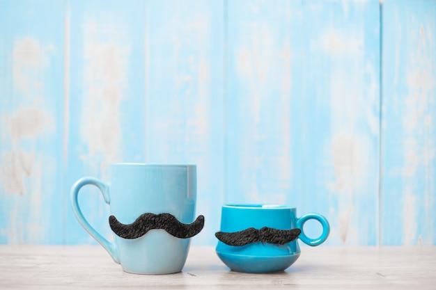 朝の木製テーブルの背景に黒口ひげと青いコーヒーカップ。父の日と国際男性デーのコンセプト Premium写真