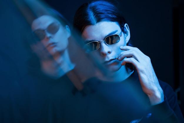 青色の照明。双子の兄弟の肖像画。ネオンと暗いスタジオで撮影したスタジオ 無料写真
