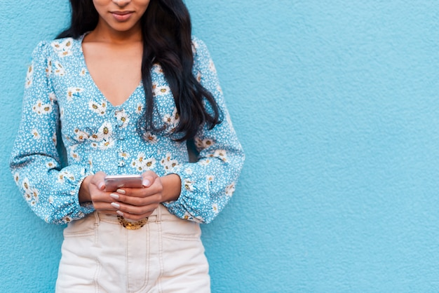 Blue copy space background and woman with phone Free Photo