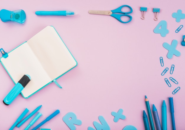 Blue craft accessories with open diary and marker arranged on pink backdrop Free Photo