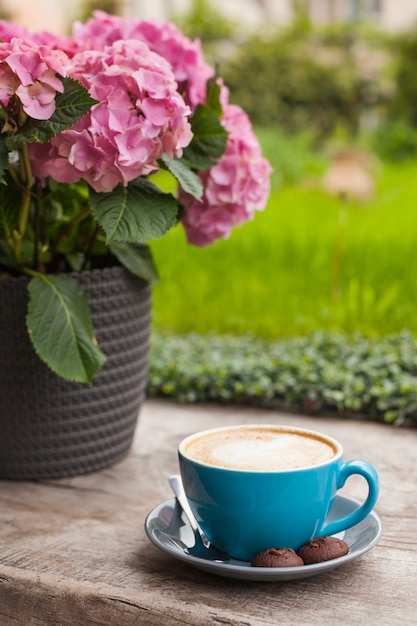 Blue cup of latte coffee with cookies on wooden surface near pink flower pot Free Photo