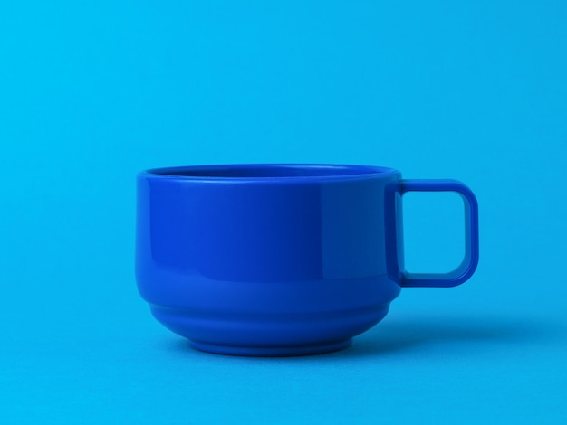 Blue cup for tea or coffee on a blue background. the style of minimalism. Premium Photo
