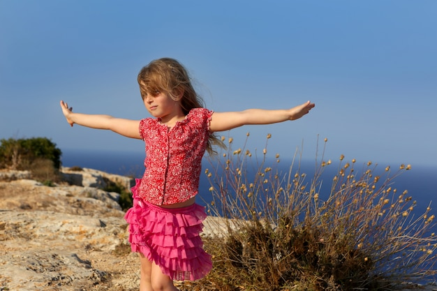 Blue day with kid girl open hands to the wind Premium Photo