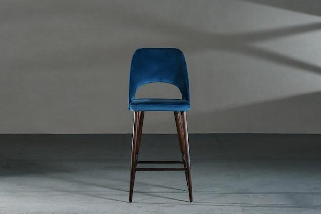 회색 벽이있는 스튜디오에서 파란색 식당 의자 무료 사진