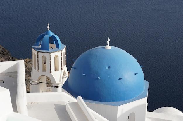 Blue dome church and whitewashed building in oia, santorini, greece Premium Photo