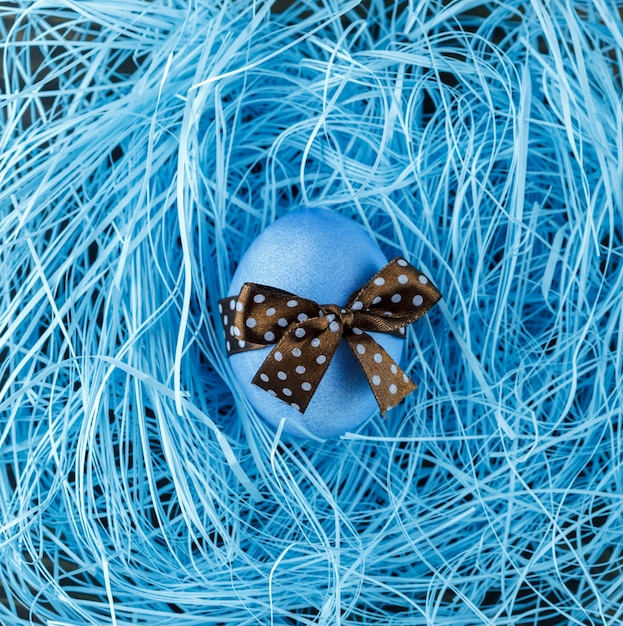 Blue easter egg with brown bow on blue background Premium Photo