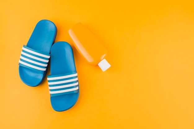 Blue flip-flops with sunscreen lotion bottle on yellow backdrop Free Photo