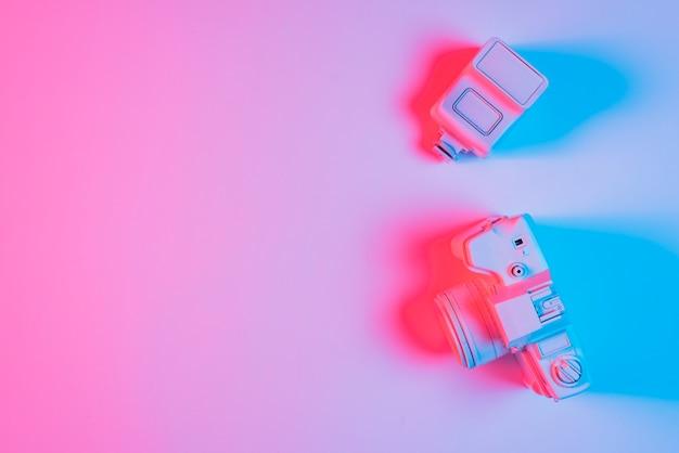塗られたカメラと無地の背景上のレンズに青いフォーカスライト 無料写真