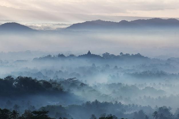 The blue fog during sunrise on borobudur temple, indonesia Premium Photo