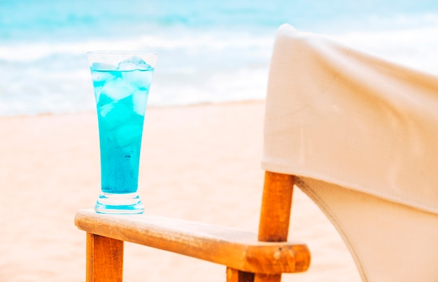 Blue fresh drink on arm of wooden chair Free Photo