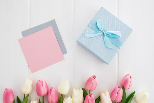 Blue gift with greeting card and tulips on white wooden background for mother's day Free Photo