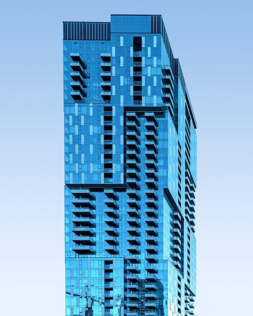 Grattacielo di vetro blu sotto il cielo blu chiaro Foto Gratuite