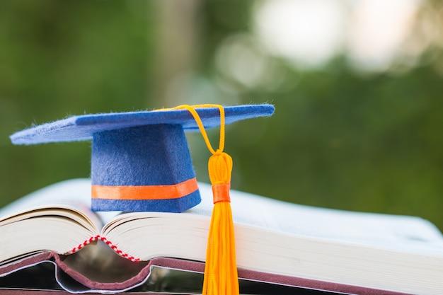 ライトグリーンと教科書を開くに青い卒業キャップ Premium写真