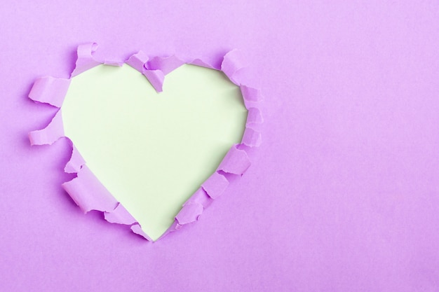 Blue heart shape hole through purple paper Premium Photo
