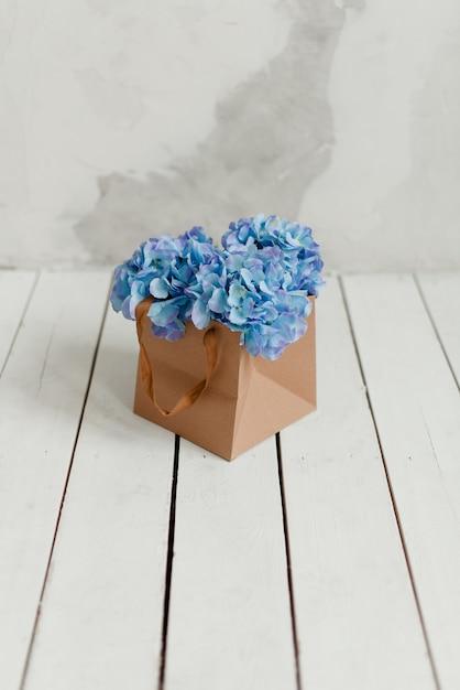 ギフトボックスに入った青いアジサイ。ギフトとしての造花。箱の中の装飾的な花。 Premium写真