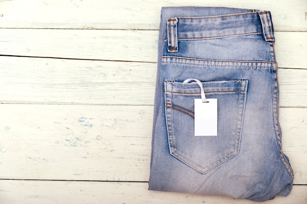 Blue jeans with blank white price label tag on shabby wooden table. Premium Photo