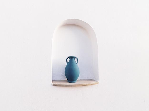 白い壁の開口部にある青い水差し-クールな背景に最適 無料写真