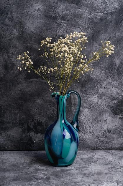 벌크 라든지와 블루 주전자 꽃병은 어두운 질감 돌 배경에 흰색 꽃을 건조, 각도보기 프리미엄 사진