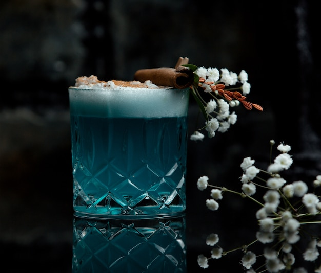 Blue lagoon cocktail glass with white foam and flower decoration Free Photo