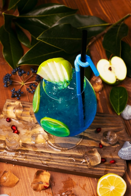 Blue lagoon cocktail with lemon slices in glass on wooden table Free Photo