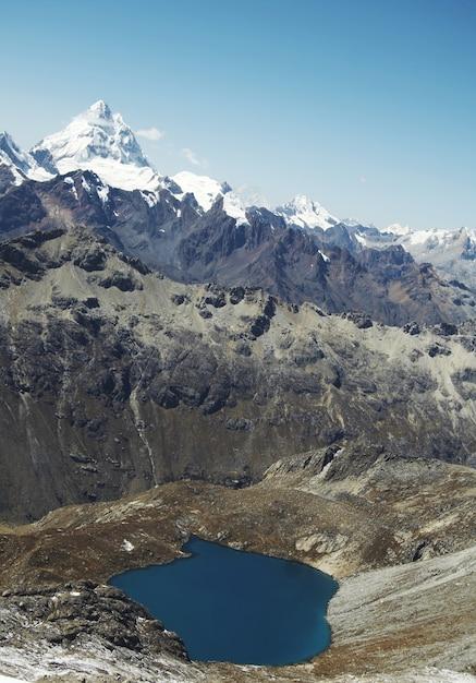 Голубое озеро и высокие снежные горы в кордильера-бланка Premium Фотографии