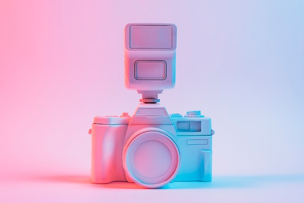 Blue light on vintage painted pink camera against pink backdrop Free Photo