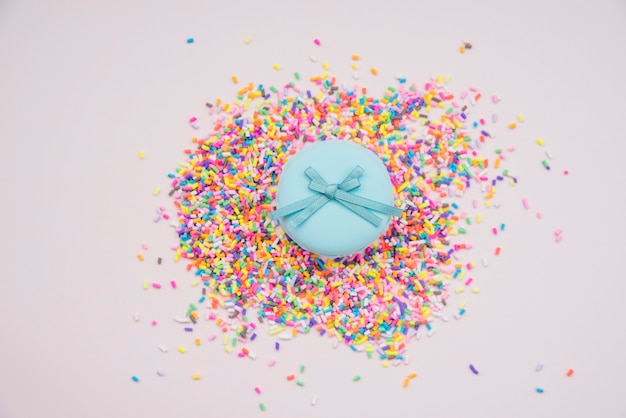Blue macarons over the colorful sprinkles on colored background Free Photo