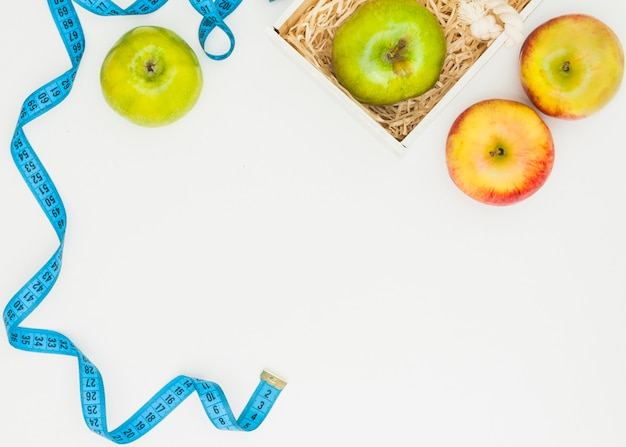 Blue measuring tape with green and red apples on white background Free Photo