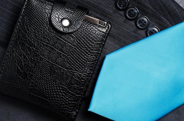Blue men's necktie, jacket sleeve, and black wallet. concept image of a successful business man Premium Photo