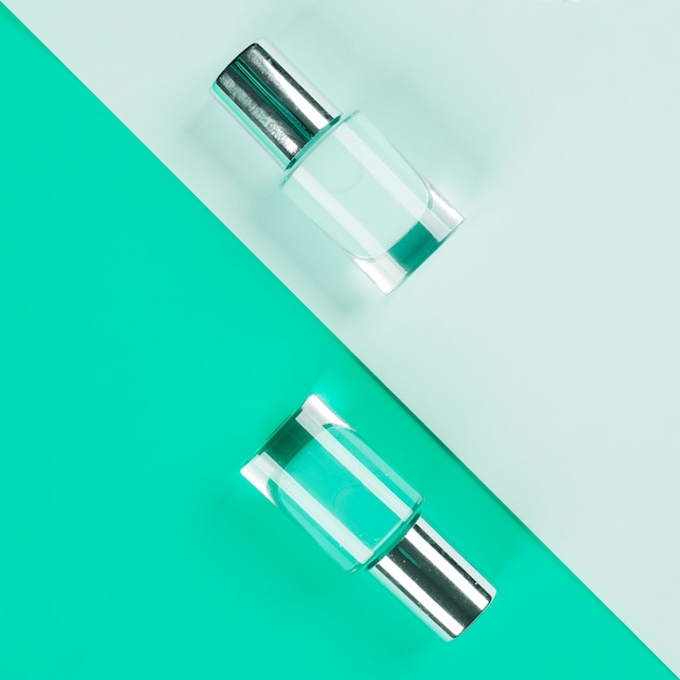 Blue and mint colored nail polish bottles on paper colored backdrop Free Photo