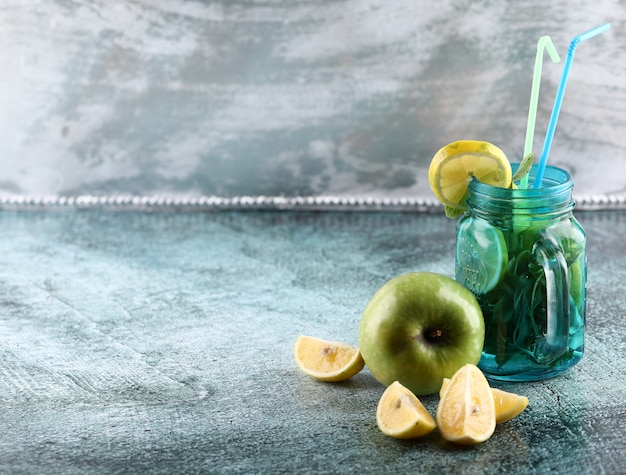A blue mojito jar with lemon, green apple and mint on shiny background with yellow and blue pipes. Free Photo