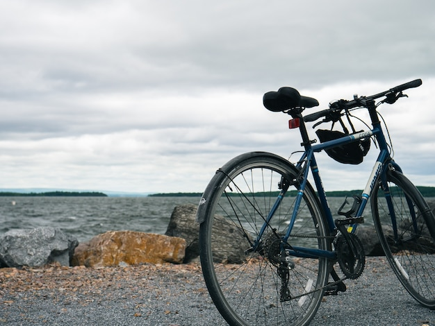 Blue mountain bike parked on a sea shore under a cloudy sky Free Photo