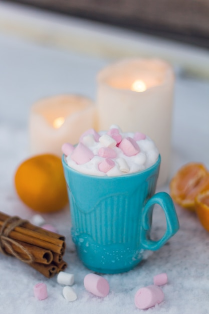 Blue mug of drink with whipped cream and marshmallows Premium Photo