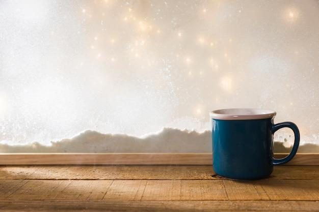 Blue mug on wood table near bank of snow and fairy lights Free Photo