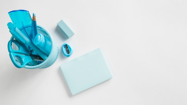Blue office supplies in cup on table Free Photo