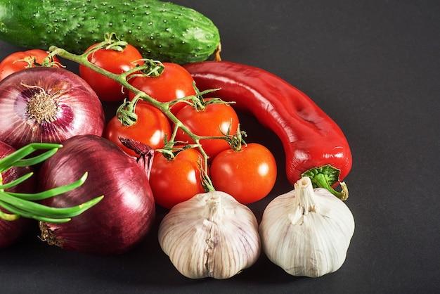 Синий лук и чеснок, помидор и огурец на черном. Бесплатные Фотографии