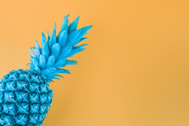 Blue painted pineapple against yellow backdrop Free Photo