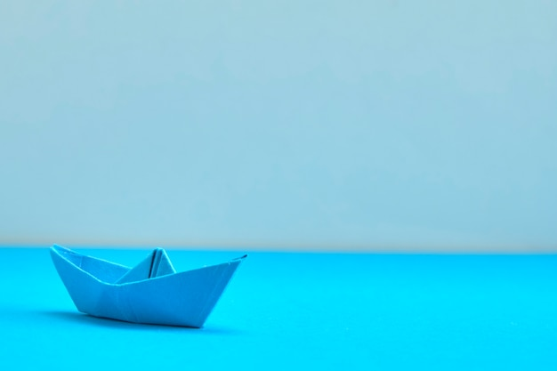 Blue paper boat on cyan background  concept for leadership