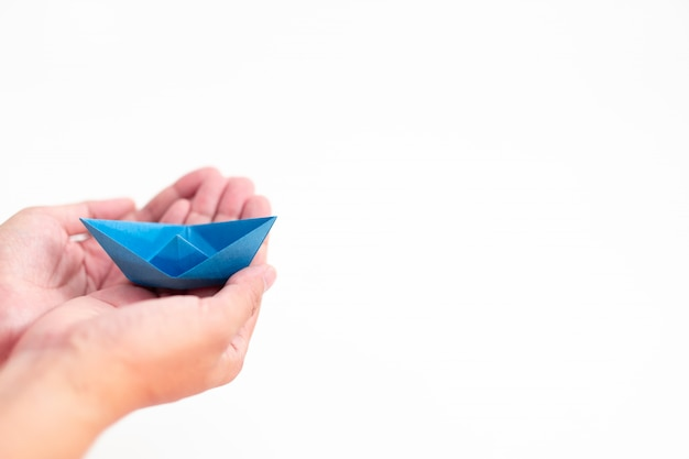 Blue paper boat holding by hand on white background, learning and education concept Premium Photo