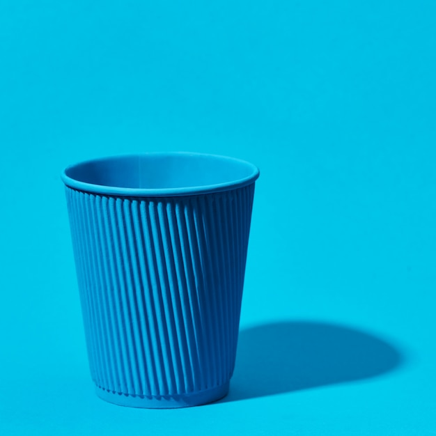 Blue paper cup standing on solid blue Premium Photo