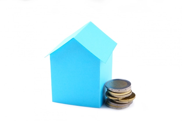 Blue paper house with coins isolated on white background Premium Photo