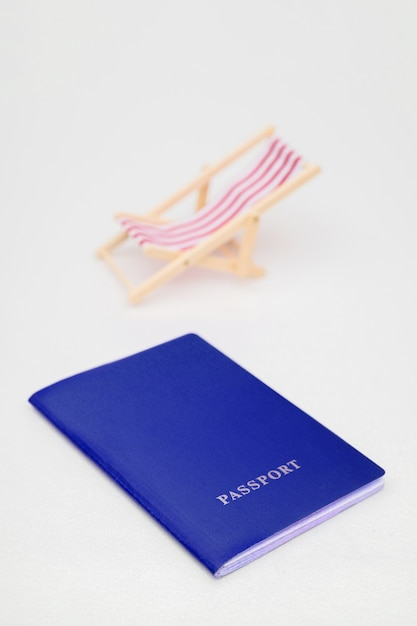 9bfeadccd4 Blue passport and red beach chair on a white background. Photo ...