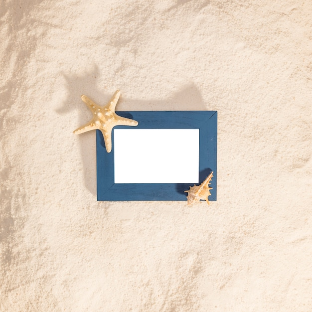 Blue photo frame with dried star on beach Free Photo