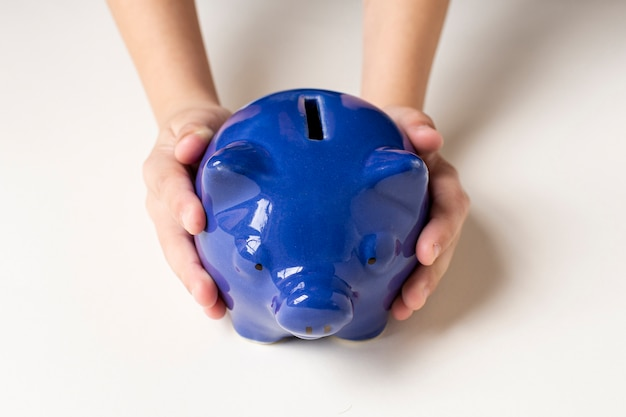 Blue piggy bank being held in hands Premium Photo