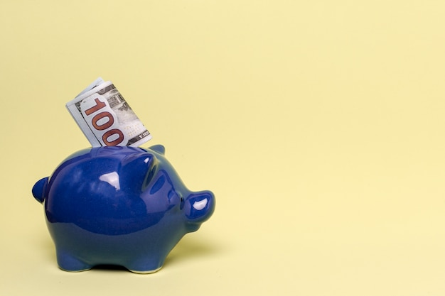 Blue piggy bank with copy space yellow background Free Photo