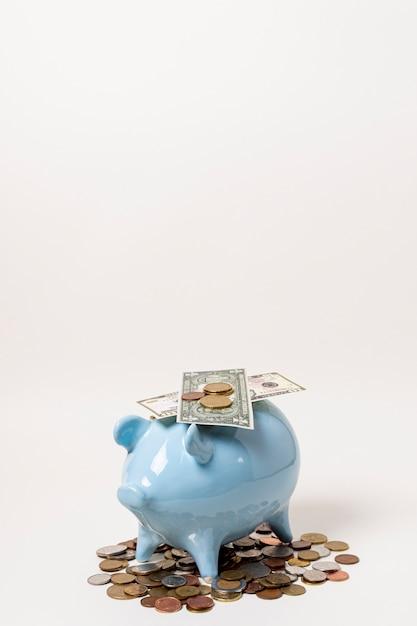お金とコインコピースペース背景に青い貯金箱 無料写真