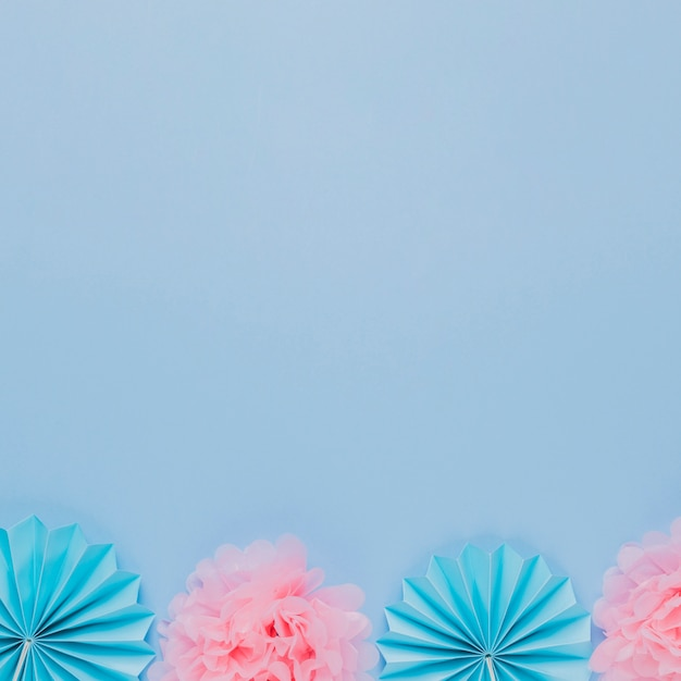 Blue and pink artistic paper flower on blue backdrop Free Photo