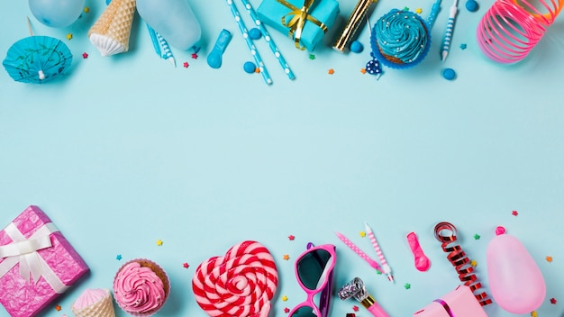Blue and pink colored muffins; gift boxes; lollipop; candles; streamer and balloon on blue backdrop Free Photo