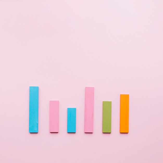 Blue; pink; green; and an orange bar in a row on pink background Free Photo