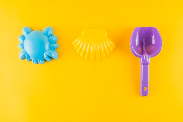 Blue plastic scallop seashell; crab and plastic shovel on yellow background Free Photo